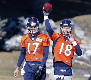 Photo - Denver Broncos quarterback Peyton Manning (18) throws a pass as backup quarterback Brock Osweiler (17) looks on during NFL football practice at the team's training facility in Englewood, Colo., on Friday, Jan. 17, 2014. The Broncos are scheduled to host the New England Patriots on Sunday for the AFC championship. (AP Photo/Ed Andrieski)