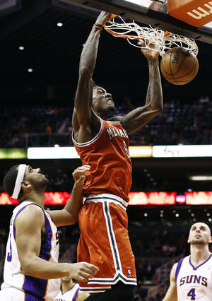 Photo - Milwaukee Bucks' Larry Sanders dunks past Phoenix Suns' Jared Dudley, left, and Marcin Gortat (4), of Poland, during the first half of an NBA basketball game, Thursday, Jan. 17, 2013, in Phoenix. (AP Photo/Ross D. Franklin)