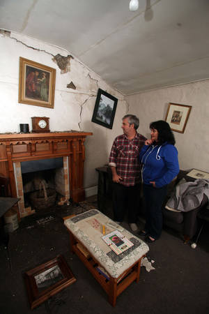 Photo - Russell and Nicola Kerslake look at their ruined house, Oak Tree Cottage, near Seddon New Zealand Friday, Aug. 16, 2013, after a magnitude-6.5 trembler. Strong earthquakes shook central New Zealand on Friday, damaging homes and roads and sending office workers scrambling for cover in the capital. No serious injuries were reported. (AP Photo/NZ Herald, Tim Cuff) AUSTRALIA OUT NEW ZEALAND OUT