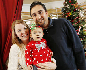 photo - Katy and Bryan Roybal and their daughter, Jane, pose for a photo  Thursday at their home in Edmond. Katy Roybal's life was saved with  22 units of blood and platelets from the Oklahoma Blood Institute when she gave birth to Jane last year. Photo by Nate Billings, The Oklahoman