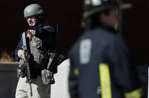 Photo - A heavily armed United States Marshall stands guard outside the Moakley Federal Court House in Boston after the building was evacuated, Wednesday, April 17, 2013.  The U.S. Marshals Service in Washington says the courthouse was evacuated due to a bomb threat. Spokeswoman Nikki Credic-Barrett says authorities are conducting a security sweep. (AP Photo/Michael Dwyer)