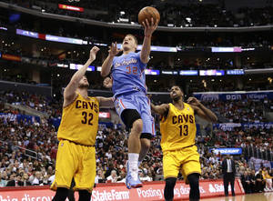 Photo - Los Angeles Clippers's Blake Griffin, center, drives to the basket past Cleveland Cavaliers's Spencer Hawes, left, and Tristan Thompson during the first half of an NBA basketball game on Sunday, March 16, 2014, in Los Angeles. (AP Photo/Jae C. Hong)