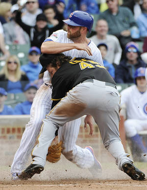 Photo - Chicago Cubs' Nate Schierholtz, top, scores on a wild pitch as Pittsburgh Pirates starting pitcher Gerrit Cole (45) makes a late tag during the fourth inning of a baseball game on Thursday, April 10, 2014 in Chicago. (AP Photo/David Banks)