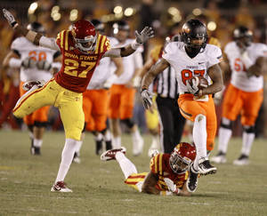 Photo - Oklahoma State's Tracy Moore (87) runs past Iowa State's C.J. Morgan (27) and Ter'Ran Benton (22) during a college football game between the Oklahoma State University Cowboys (OSU) and the Iowa State University Cyclones (ISU) at Jack Trice Stadium in Ames, Iowa, Friday, Nov. 18, 2011. Photo by Bryan Terry, The Oklahoman