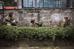 "Photo - Kenya security forces are seen behind a wall outside the Westgate Mall in Nairobi, Kenya Monday morning, Sept. 23, 2013. Kenya's military launched a major operation at the upscale Nairobi mall and said it had rescued ""most"" of the hostages being held captive by al-Qaida-linked militants during the standoff that killed at least 68 people and injured 175. (AP Photo/Jerome Delay)"
