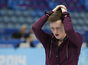 Photo - Jeremy Abbott of the United States holds his head as he skates off the ice following the men's team short program figure skating competition at the Iceberg Skating Palace during the 2014 Winter Olympics, Thursday, Feb. 6, 2014, in Sochi, Russia. (AP Photo/Darron Cummings, Pool)