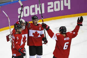 Photo - Dan Hamhuis of Canada (5), goalkeeper Carey Price of Canada (31), Jonathan Toews of Canada (16) and Shea Weber of Canada (6) celebrate their 3-0 win over Sweden in the men's gold medal ice hockey game at the 2014 Winter Olympics, Sunday, Feb. 23, 2014, in Sochi, Russia. (AP Photo/Petr David Josek)