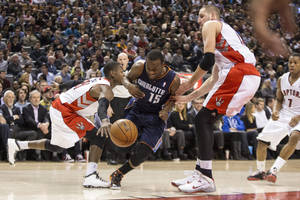 Photo - Charlotte Bobcats' Kemba Walker (drives between Toronto Raptors' Jonas Valanciunas, right, and Terrence Ross during the first half of an NBA basketball game in Toronto on Wednesday, Dec. 18, 2013. (AP Photo/The Canadian Press, Chris Young)