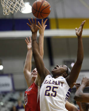 Photo - Stony Brook forward Brittany Snow (20) and Albany forward Shereesha Richards (25), of Jamaica, battle for a rebound during the first half of an NCAA America East college championship basketball game on Monday, March 10, 2014, in Albany, N.Y. (AP Photo/Mike Groll)