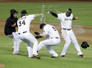 Photo - Miami Marlins second baseman Ed Lucas, second from right, is doused with water by teammates after he hit a single in the 11th inning scoring Jeff Baker to defeat the Philadelphia Phillies 5-4 during a baseball game, Tuesday, July 1, 2014 in Miami. Teammates, from left, Henderson Alvarez, Tom Koehler and Marcell Ozuna. (AP Photo/Wilfredo Lee)