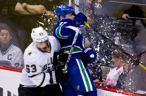 Photo -   Dallas Stars' Mike Ribeiro, left, checks Vancouver Canucks' Aaron Rome during the third period of an NHL hockey game in Vancouver, British Columbia, on Tuesday March 6, 2012. (AP Photo/The Canadian Press, Darryl Dyck)