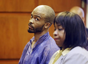 Photo - Michael Madison glances at court-appointed attorney Marlene Rideenour during his arraignment in East Cleveland on Monday, July 22, 2013. Madison has been charged with aggravated murder in the deaths of three women found in garbage bags in the city over the weekend. (AP Photo/Mark Duncan)