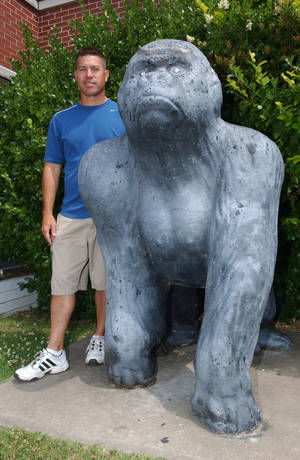 Photo - Willie Ng, who was quarterback of the Picher Gorillas in 1984 when the school won the state championship, poses with the gorilla mascot statue that will be sold at auction on Sunday. Ng is now head football coach at Commerce High School. Photo by Gary Crow, for The Oklahoman
