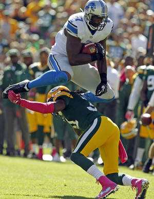 Photo - FILE - In this Oct. 6, 2013 file photo, Detroit Lions' Brandon Pettigrew tries to leap over Green Bay Packers' Davon House after a catch during the first half of an NFL football game in Green Bay, Wis. A person familiar with the negotiations says the Lions have re-signed Pettigrew to a $16 million, four-year contract. The person, who says $8 million is guaranteed, spoke Friday, March 14, 2014, to The Associated Press on condition of anonymity because the deal had not been announced. (AP Photo/Mike Roemer, File)