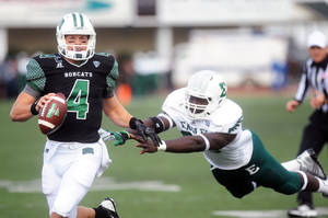 Photo - Ohio University quarterback Tyler Tettleton tries to evade an Eastern Michigan defender in the second quarter of an NCAA college football game Saturday, Oct. 19, 2013, in Ypsilanti, Mich. Ohio won 56-28. AP Photo/The Ann Arbor News, Brianne Bowen