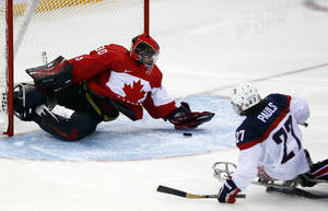 Photo - United States' Joshua Pauls, right, shoots on goal as Canada's goaltender Corbin Watson tries to defend during the ice sledge hockey semifinal match at the 2014 Winter Paralympics in Sochi, Russia, Thursday March 13, 2014. United States won 3-0. (AP Photo/Pavel Golovkin)