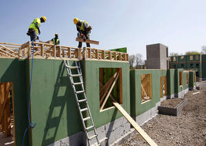 Photo - In this Wednesday, April 24, 2013, photo, workers are seen at the construction of a new apartment housing complex in Trenton, N.J. The Commerce Department reports the pace at which builders broke ground on homes in April on Thursday, May 16, 2013. (AP Photo/Mel Evans)