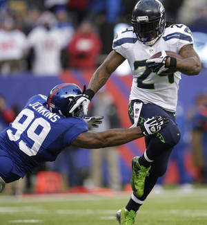 Photo - Seattle Seahawks running back Marshawn Lynch (24) avoids the tackle attempt of New York Giants defensive tackle Cullen Jenkins (99) during the second half of an NFL football game, Sunday, Dec. 15, 2013, in East Rutherford, N.J. (AP Photo/Kathy Willens)