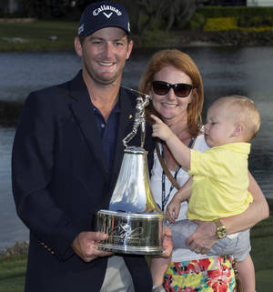 Photo - Matt Every, left, his wife Danielle and their son Liam pose with the trophy after the Arnold Palmer Invitational golf tournament at Bay Hill, Sunday, March 23, 2014, in Orlando, Fla. (AP Photo/Willie J. Allen Jr.)