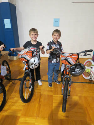 Photo - First-graders Travis Bailey, left, and Logan Libby were among the more than 50 students who received the surprise of a new bike and helmet  at Orvis Risner Elementary School in Edmond. PHOTO PROVIDED BY EDMOND PUBLIC SCHOOLS.    <strong></strong>