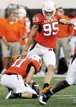 photo - OSU's Dan Bailey (95) kicks a 49-yard field goal as Wes Harlan (11) holds in the first quarter during the college football game between the University of Tulsa (TU) and Oklahoma State University (OSU) at Boone Pickens Stadium in Stillwater, Oklahoma, Saturday, September 18, 2010. Photo by Nate Billings, The Oklahoman