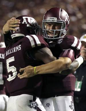 Photo - Texas A&M quarterback Johnny Manziel, right, celebrates with teammate Brandon Williams (5) after throwing a touchdown pass to Williams during the third quarter of an NCAA college football game against Sam Houston State, Saturday, Sept. 7, 2013, in College Station, Texas. (AP Photo/David J. Phillip)