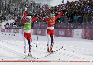Photo - Norway's Marit Bjoergen, left, and Ingvild Flugstad Oestberg celebrate winning the gold medal in the cross-country team sprint competitions at the 2014 Winter Olympics, Wednesday, Feb. 19, 2014, in Krasnaya Polyana, Russia. (AP Photo/Lee Jin-man)