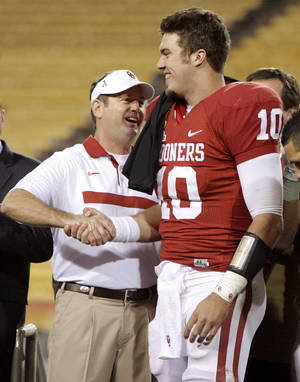 Photo - Oklahoma coach Bob Stoops shakes hands with Oklahoma's Blake Bell (10) after Bell was named the offensive player of the game following Oklahom's win in the Insight Bowl college football game between the University of Oklahoma (OU) Sooners and the Iowa Hawkeyes at Sun Devil Stadium in Tempe, Ariz., Friday, Dec. 30, 2011. Photo by Bryan Terry, The Oklahoman