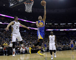 Photo - Golden State Warriors point guard Stephen Curry (30) drives past New Orleans Pelicans shooting guard Austin Rivers (25) and point guard Tyreke Evans (1) during the first half of an NBA basketball game in New Orleans, Saturday, Jan. 18, 2014. (AP Photo/Jonathan Bachman)