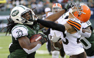 Photo - onNew York Jets running back Chris Ivory (33) stiff-arms Cleveland Browns' Joe Haden (23) during the second half of an NFL football game on Sunday, Dec. 22, 2013, in East Rutherford, N.J. (AP Photo/Bill Kostroun)
