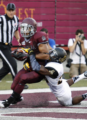 Photo - Montana wide receiver Chase Naccarato (5) catches a touchdown pass as Appalachian State defensive back Joel Ross (26) defends during the second quarter of an NCAA college football game in Missoula, Mont., Saturday, Aug. 31, 2013. (AP Photo/Michael Albans)