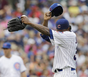 Photo - Chicago Cubs starter Edwin Jackson wipes his face after Atlanta Braves' Chris Johnson hit a two-run double during the fourth inning of a baseball game in Chicago, Saturday, July 12, 2014. (AP Photo/Nam Y. Huh)