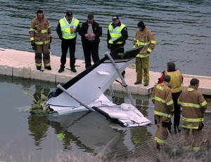 Photo - This photo provided by the Ouray County Plaindealer shows rescue personnel examining the tail second of a plane on Saturday, March 22, 2014 after it was recovered from the Ridgeway Reservoir south of Montrose. Colo. The plane believed to be carrying five people crashed into a reservoir in southwestern Colorado and authorities say all are feared dead. Divers are to be used Sunday to search for victims and to recover the rest of the plane. (AP Photo/Ouray County Plaindealer, Patrick Moore)  MANDATORY CREDIT