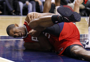 Photo -   Atlanta Hawks center Al Horford grimaces in pain after he was injured in the first half of an NBA basketball game against the Indiana Pacers in Indianapolis, Wednesday, Jan. 11, 2012. (AP Photo/Michael Conroy)
