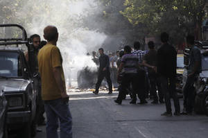 Photo -   This photo, taken by an individual not employed by the Associated Press and obtained by the AP outside Iran shows, Iranians stand in a street as a garbage can is set on fire, in central Tehran, near Tehran's old main bazaar, on Wednesday, Oct. 3, 2012. Police threatened merchants who closed their shops in Tehran's main bazaar and launched crackdowns on sidewalk money changers on Wednesday as part of a push to halt the plunge of Iran's currency, which has shed more than a third its value in less than a week. (AP Photo) EDITORS NOTE AS A RESULT OF AN OFFICIAL IRANIAN GOVERNMENT BAN ON FOREIGN MEDIA COVERING SOME EVENTS IN IRAN, THE AP WAS PREVENTED FROM INDEPENDENT ACCESS TO THIS EVENT.