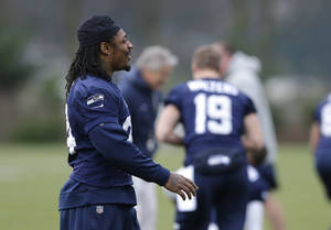Photo - Seattle Seahawks NFL football running back Marshawn Lynch, left, walks during stretching warmups on Thursday, Jan. 2, 2014, before practice in Renton, Wash. (AP Photo/Ted S. Warren)