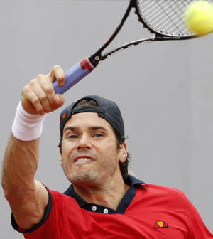 Photo - Germany's Tommy Haas grimaces as he returns during the first round match of the French Open tennis tournament against Estonia's Jurgen Zopp at the Roland Garros stadium, in Paris, France, Tuesday, May 27, 2014. Haas was forced to retire with a right shoulder injury. (AP Photo/Darko Vojinovic)