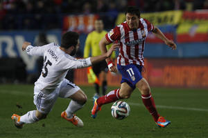 Photo - Atletico's Cristian Rodriguez in action with Real's Daniel Carvajal during a semi final, 2nd leg, Copa del Rey soccer derby match between Real Madrid and Atletico Madrid at the Vicente Calderon Stadium in Madrid, Tuesday Feb. 11 , 2014.  (AP Photo/Gabriel Pecot)