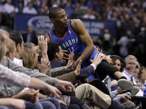 Photo - Oklahoma City Thunder's Russell Westbrook falls into the front row of fans chasing down a loose ball in the second half of an NBA basketball game against the Dallas Maverick,s Wednesday, Feb. 1, 2012, in Dallas. Westbrook had a game-high 33 points in the 95-86 Thunder win. (AP Photo/Tony Gutierrez) ORG XMIT: DNA114