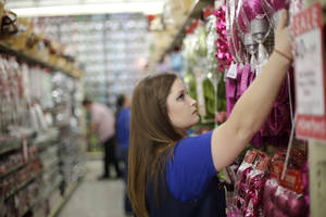 Photo - Hobby Lobby employee Megan Moran stocks the shelves with Christmas  merchandise.
