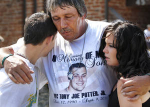photo - Wearing a shirt honoring his son, Tony Potter, Sr. hugs his daughter, Christy,   and another son, Dillon, after the Memorial Day Ceremony on the grounds of the 45th Infantry Division Museum  on Monday,  May 28,  2012,  Potter is from Okmulgee. His son, PFC Tony Potter, Jr.,  was killed in Afghanistan in September, 2011, while serving with the Oklahoma National Guard. Photo by Jim Beckel, The Oklahoman