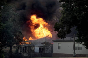 Photo - A home burns in Luther, Okla.,  during a large wildfire Friday, Aug. 3, 2012. <strong>SARAH PHIPPS - THE OKLAHOMAN</strong>