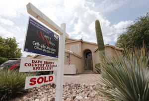 Photo - FILE - In this Thursday, Aug. 22, 2013, file photo, an existing home is listed as sold, in Gilbert, Ariz. Freddie Mac, on Thursday, Dec. 12,  2013, reports on mortgage rates for the week. (AP Photo/Matt York, File)