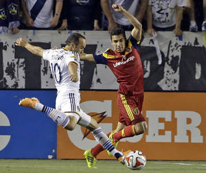 Photo - Real Salt Lake defender Tony Beltran covers as Los Angeles Galaxy midfielder Landon Donovan attacks in the first half of an MLS soccer game in Carson, Calif., Saturday, March 8, 2014.  Real Salt Lake won, 1-0. (AP Photo/Reed Saxon)