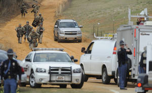 photo - Heavily armed men move away from the suspects home at the scene of a Dale County hostage scene in Midland City, Ala. on Wednesday Jan. 30, 2013. Authorities were locked in a standoff Wednesday with a gunman authorities say on Tuesday intercepted a school bus, killed the driver, snatched a 6-year-old boy and retreated into a bunker at his home in Alabama. (AP Photo/Montgomery Advertiser, Mickey Welsh)  NO SALES