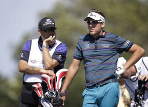 Photo - Ian Poulter of England, right, waits his turn with caddie Terry Mundy on the fourth tee during the second round of the Cadillac Championship golf tournament Friday, March 7, 2014, in Doral, Fla. (AP Photo/Wilfredo Lee)