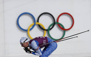 Photo - Estonia's Indrek Tobreluts skis past the Olympic rings during a biathlon training session at the 2014 Winter Olympics, Friday, Feb. 7, 2014, in Krasnaya Polyana, Russia. (AP Photo/Felipe Dana)