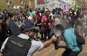 Photo - Military police uses pepper gas during protests after the military ceremony of Independence Day in Brasilia, Brazil, Saturday, Sept. 7, 2013.  Brazilians are protesting against corruption and poor public services despite a heavy tax burden.  (AP Photo/Eraldo Peres)