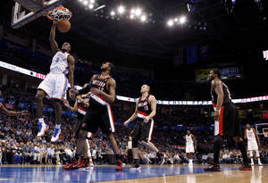 Photo - Oklahoma City's Serge Ibaka (9) dunks the ballduring the NBA basketball game between the Oklahoma City Thunder and the Portland Trailblazers at Chesapeake Energy Arena in Oklahoma City, Sunday, March 18, 2012. Photo by Sarah Phipps, The Oklahoman.