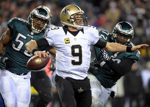 Photo - Saints quarterback Drew Brees, (9) throws the ball as he is pressured by Eagles linebacker Brandon Graham, (55) and defensive end Cedric Thornton (72) during an NFL wild-card playoff football game, Saturday, Jan. 4, 2014, in Philadelphia. (AP Photo/The Express-Times, Matt Smith)